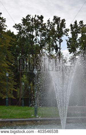 Fountain Of Water In The Foreground On A Cloudy Summer Day. Fountain In Park. Hot Summer Day. Beauti