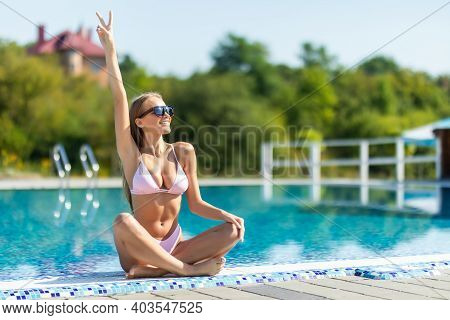 Young Woman With Hands Up In Pink Bathing Suit In Pool