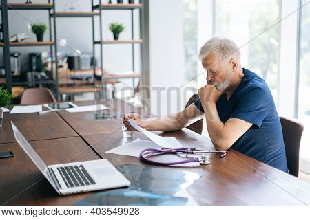 Focused Thoughtful Gray-haired Mature Man Doctor Studying Medical Report Of Patient, Working With Pa