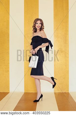 Beautiful Woman Fashion Model Holding Shopping Bag On Gold Background