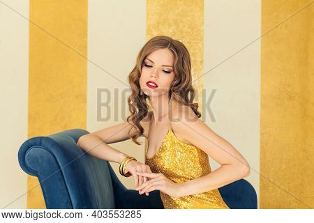 Nice Celebrity Woman With Curly Hairstyle Against Golden Stucco Wall Background