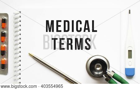 Medical Terms Is Written In A Notebook On A White Table Next To Pills And A Stethoscope. Medical Con