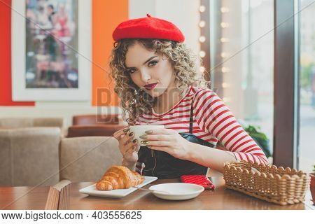 Attractive Young  Woman Drinking Coffee In Cafe