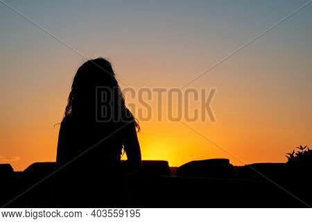 Silhouette Of A Woman Practising Yoga In The Evening.woman Thinking And Observing The Sunset. Horizo