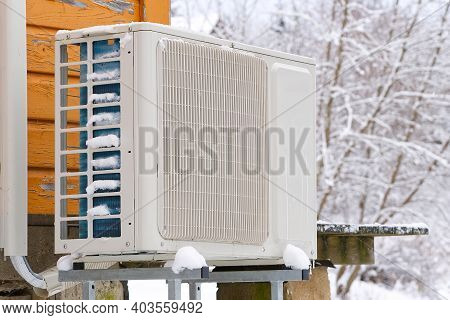 Air To Water Heat Pump Near An Old Wooden House In Winter. Air Water Heatpump Close Up