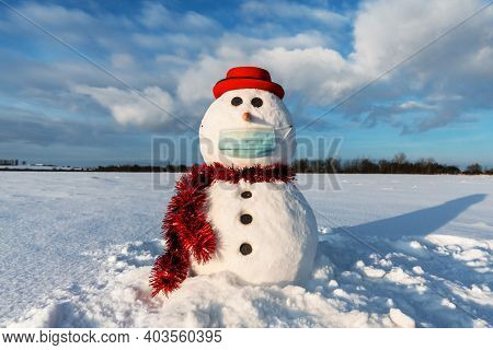 Funny snowman in stylish red hat with medical mask on snowy field. Canceled travel and social distancing concept