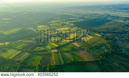 Above View Over Green Haze Hilly Landscape, Several Cultivated, Arable Plots, Among Forest Trees In