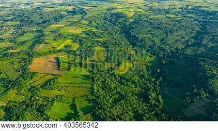 Above View Over Green Hilly Landscape, Several Cultivated, Arable Plots, Among Forest Trees.