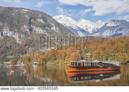 Pleasure Boat And Two Rowers On The Picturesque Lake Bohinj. Triglav National Park In Slovenia In Au