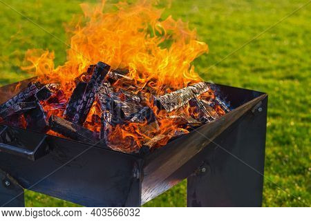 The Concept Of A Picnic. Fire During A Picnic On A Green Lawn For A Picnic With A Blurred Background