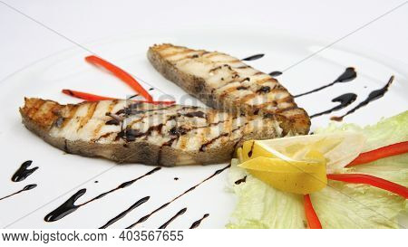 Grilled Seafood Halibut With Lemon, Red Pepper And Green Lettuce On White Plate. Close-up Photo