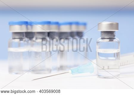 Vials And Syringe With Vaccine Against Covid-19 - Focus On The Vial In The Foreground