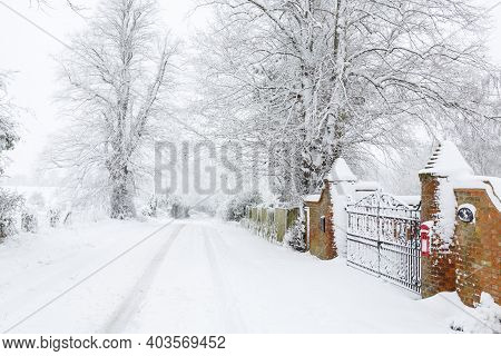 Snow Covered British Road Outside Entrance To An Old House Surrounded By Countryside In Winter