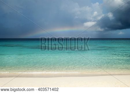 The View Of Grand Turk Island Beach With Dark Rainy Sky And A Rainbow In A Background (turks And Cai