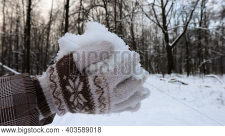 Women's Hands In Knitted Mittens Hold Natural Soft White Snow Outside On A Winter Day. Joyful Winter