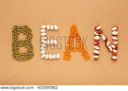 Creative Layout Made Of Beans And Lentils On The Cork Background Flat Lay. Word Bean, Food Concept,