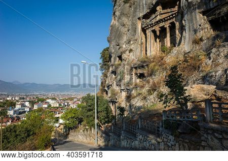Ancient Lycian Rock Tombs on mountain cliff, view of Fethiye town from the hill, Turkey