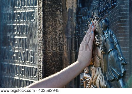 Prague - August 07, 2016: Tourist Hand Touches A Bronze Bas-relief At The Foot Of The Monument To Ja