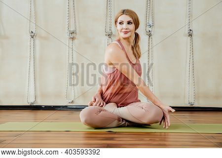 Mature Woman Practicing Yoga Sitting In Twisting Pose On A Floor