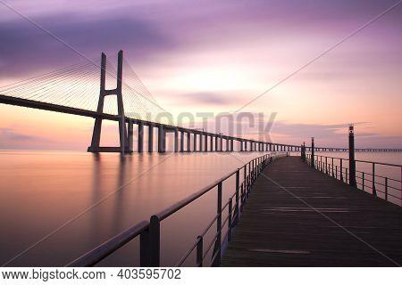 Long Exposure Shot At Daybreak On Vasco Da Gama Bridge. Lisbon, Portugal. Space For Text.