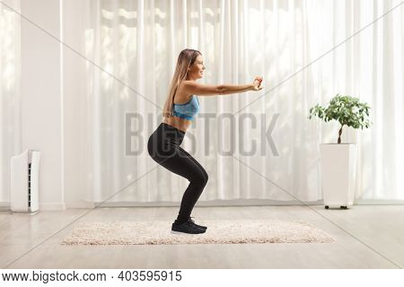 Full length profile shot of a young woman in tights and sports top exercising at home