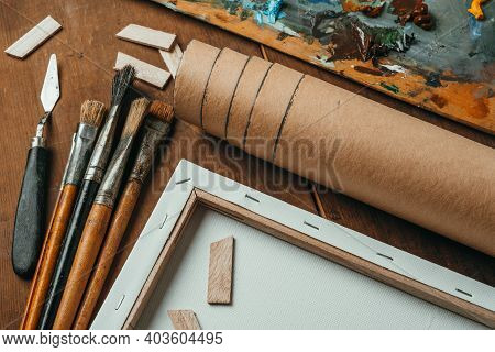 Brushes Made Of Bristles, A Roll Of Craft Paper, Palette Knife, Stretcher, And Palette Are On Wooden