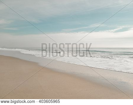 A Minimal Beach Shore. Soft Wave Of The Ocean On The Sandy Beach. Rockaway Beach, New York.