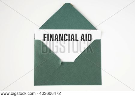 Financial Aid Text On White Paper In A Green Envelope.