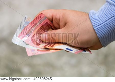Man Hands Giving Money. Holding Euro Banknotes On A Blurred Background, Eu Currency