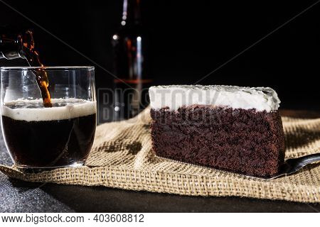 Portion Of Chocolate Cake And Black Beer On Black Background