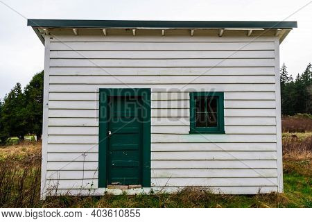 The Side Of An Old Shed With White Siding And A Green Window And Door.