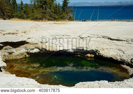 A Colorful Pool In The West Thumb Geyser Basin At Yellowstone National Park, With Yellowstone Lake I