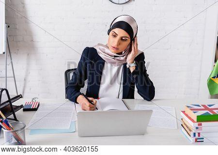 Arabian Interpreter In Headset Writing In Notebook Near Laptop, Digital Translator And Dictionaries