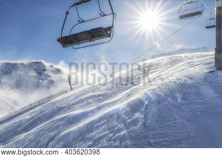 Chairlift From A Ski Resort On A Sunny Day With The Sun In The Background And A Blizzard Breeze On T