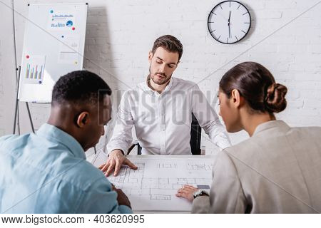 Multicultural Businesspeople Looking At Blueprint Near Interpreter And Flipchart With Infographics O
