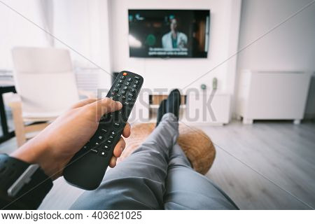 Man Sitting On Sofa And Watching Tv With Remote Controller In His Hand. Rest At Home.