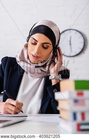 Arabian Translator In Headset Writing Near Dictionaries Of Foreign Languages On Blurred Foreground