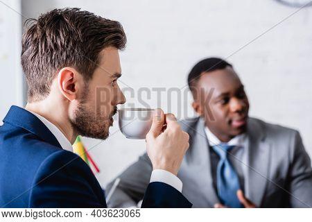 Interpreter Drinking Coffee Near African American Business Partner On Blurred Background