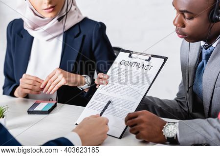 Cropped View Of Interpreter Pointing With Pen At Contract Near African American And Arabian Business
