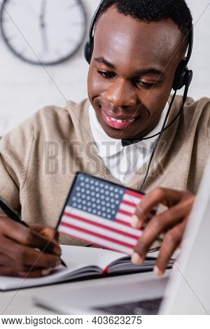 Smiling African American Interpreter In Headset Writing In Notebook While Holding Digital Translator
