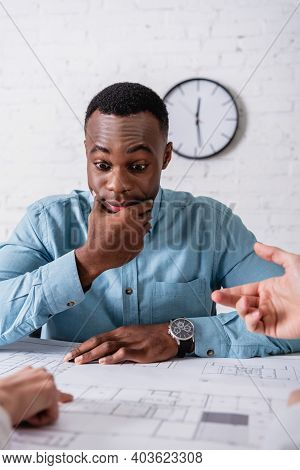 Discouraged African American Businessman Looking At Blueprint Near Business Partners Gesturing On Bl