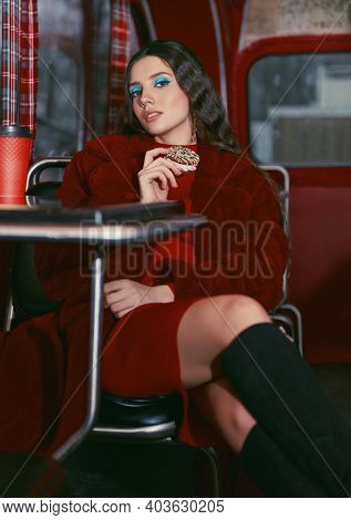 Pretty Girl Sitting In Cafe Bus (bistro), And Eating A Biscuit. Retro (vintage) Portrait Of Beautifu
