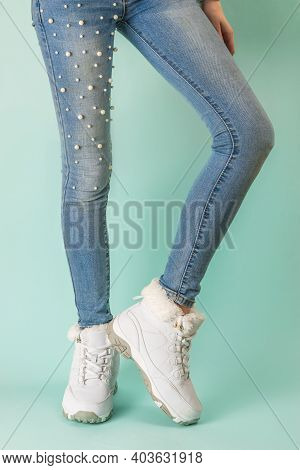 Slim Female Legs In Tight Jeans And White Sneakers On A Blue Background. Winter Sports Style.