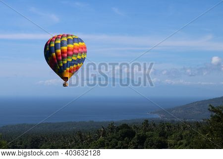 Colorful Hot Air Balloon Fly Over The Blue Sea. Big Blue Hot Air Balloon Flying In Light Blue Sky Wi