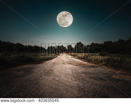 Landscape Of Night Sky And Bright Full Moon Above Wilderness Area. Asphalt Road Leading Into The For