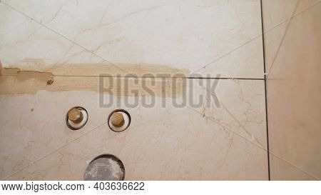 Close-up Side View Of A Builder Applying Tiles And Spacers Between Tiles That Have Been Securely App
