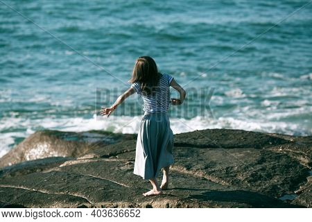 The young dancers woman is engaged in choreography on the rocky coast of ocean.