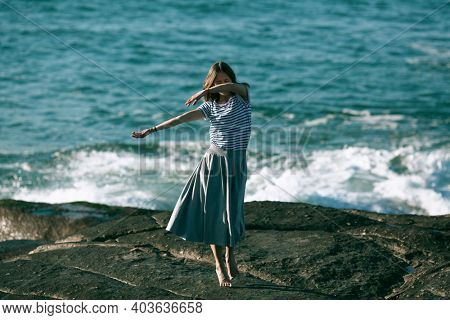 Young dancers woman is engaged in choreography on the rocky coast of the ocean.