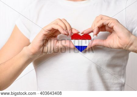 Love Netherlands. The Girl Holds A Heart In The Form Of The Flag Of The Netherlands On Her Chest. Du