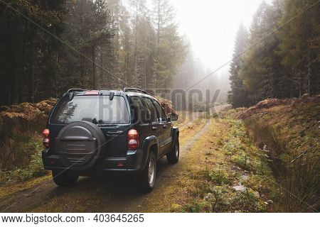 Scotland, Uk - October 19, 2006. A 4x4 Suv Car Drives Off-road Through A Forest In The Highlands Of